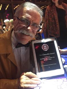 Dr Tim Mooney collecting Dr Chris Hughes' award