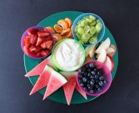 Chopped fresh fruit (mix of fruits) and a yoghurt dip arranged as a platter