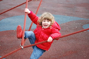 Young child playing on playground equipment