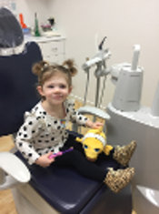 child in a dental chair smiling